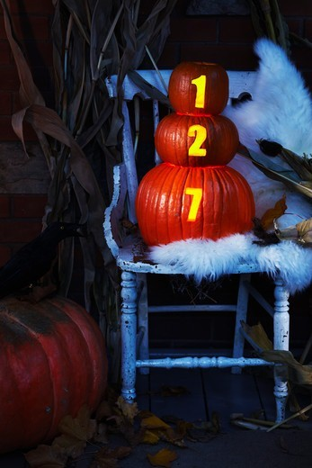 Stock Photo: 1828R-92634 Front Porch Decorated for Halloween with Chair and Pumpkins with House Number Illuminated, Toronto, Ontario, Canada