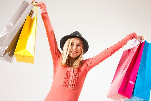 Stock Photo: 1828R-92884 Low Angle View Portrait of Blond, Teenage Girl wearing Hat and holding Shopping Bags in Air, Studio Shot on White Background