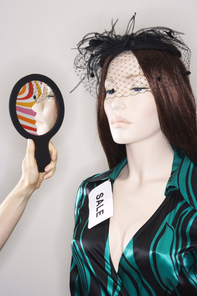 Stock Photo: 1828R-9373 Woman Holding Mirror By Mannequin