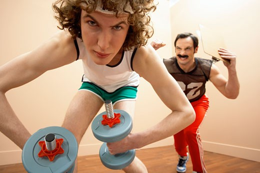 Stock Photo: 1828R-9477 Man Lifting Weights, Personal Trainer in the Background