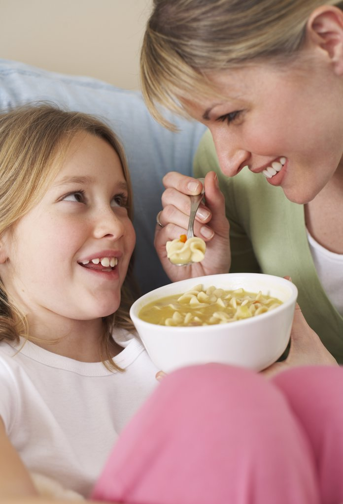 Stock Photo: 1828R-9747 Mother and Daughter Eating Chicken Soup