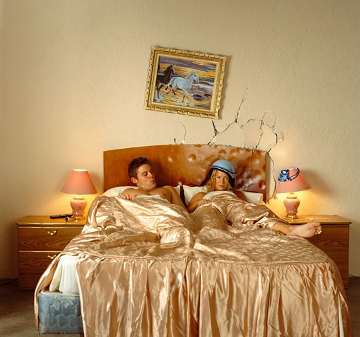 Couple in Bed with Dented Headboard : Stock Photo