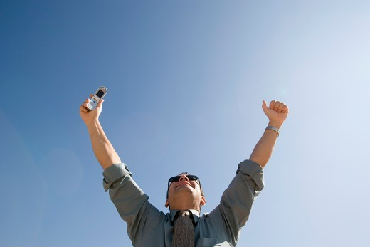Businessman with Cell Phone Celebrating : Stock Photo