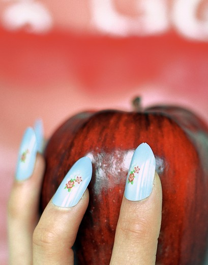 Woman's Hand Holding Apple by Liz Wolfe : Stock Photo