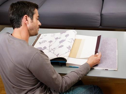 Man Looking at Wallpaper Samples : Stock Photo