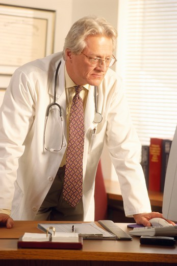 Doctor Consulting Computer at Desk : Stock Photo