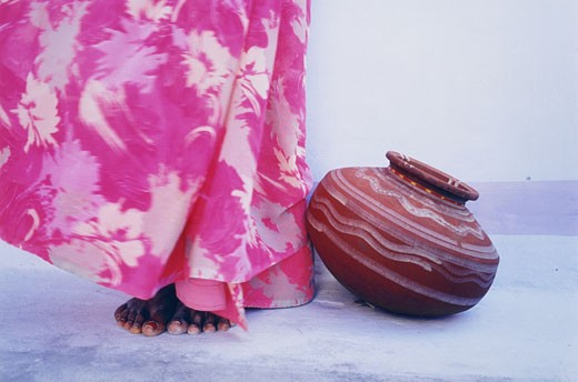 Woman in pink sari standing beside a jug, India : Stock Photo