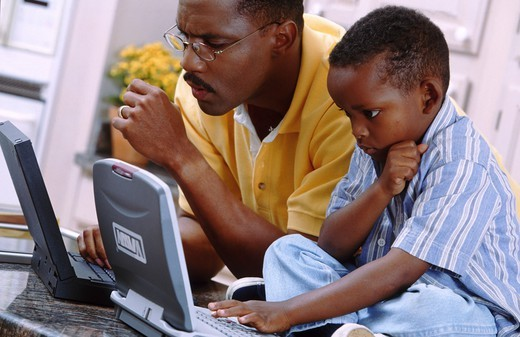 Father and son with laptop computers : Stock Photo