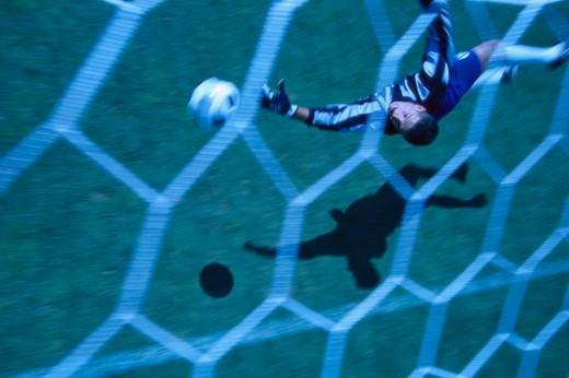 Soccer Goalie Going for the Ball : Stock Photo