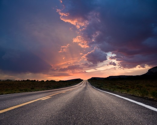 Road passing through a landscape at sunrise : Stock Photo
