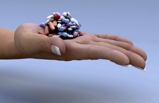 An open human palm holding a pile of pills : Stock Photo