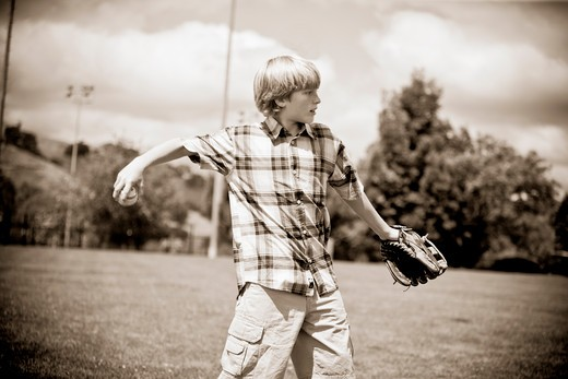 Stock Photo: 1833-202 Boy playing baseball in a field