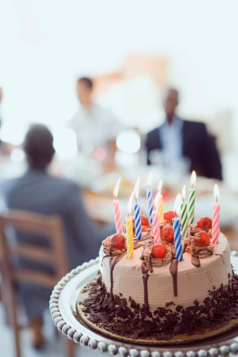 Close-up of a birthday cake with three people sitting at the dining table in the background : Stock Photo
