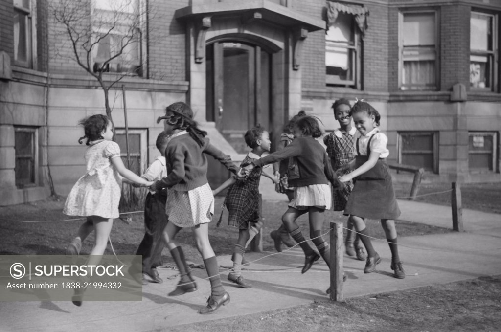 """Stock Photo: 1838-21994332 Group of Girls Playing Ring-Around-a-Rosie on Sidewalk in """"Black Belt"""" Neighborhood, Chicago, Illinois, USA, Edwin Rosskam for Office of War Information, April 1941"""
