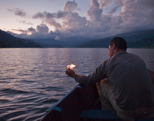 Man on Boat Burning Piece of Paper at Dusk : Stock Photo