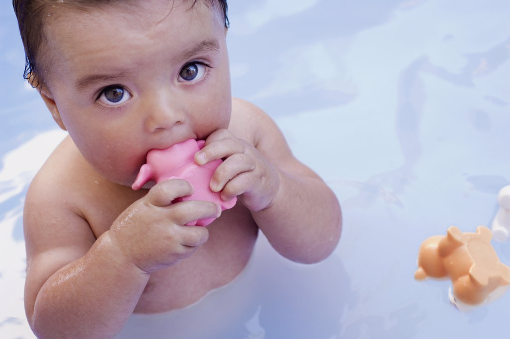 Baby Taking Bath with Plastic Toy in it's Mouth : Stock Photo