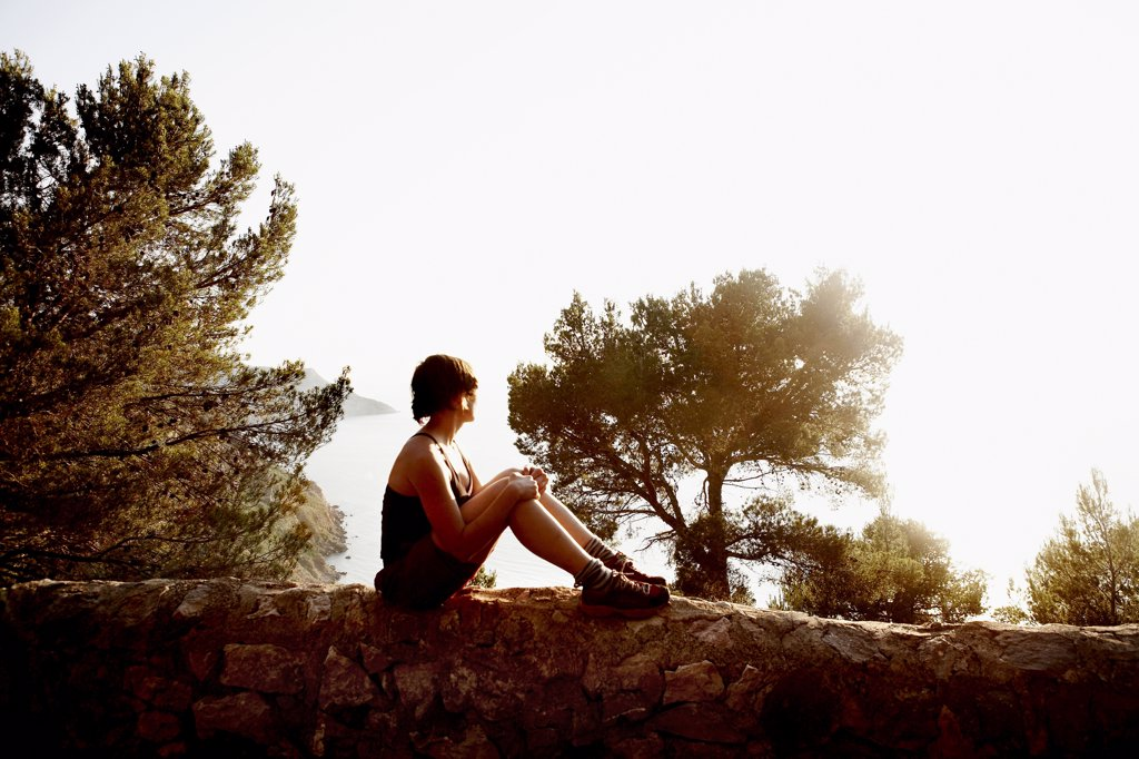 Stock Photo: 1838-10899 Woman Sitting on Rock Wall and Looking at Mediterranean Sea, Mallorca, Spain