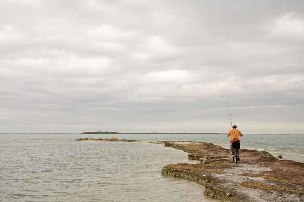 Stock Photo: 1838-11908 Man Riding Bicycle With Fishing Rods on Beach, Florida Keys, USA