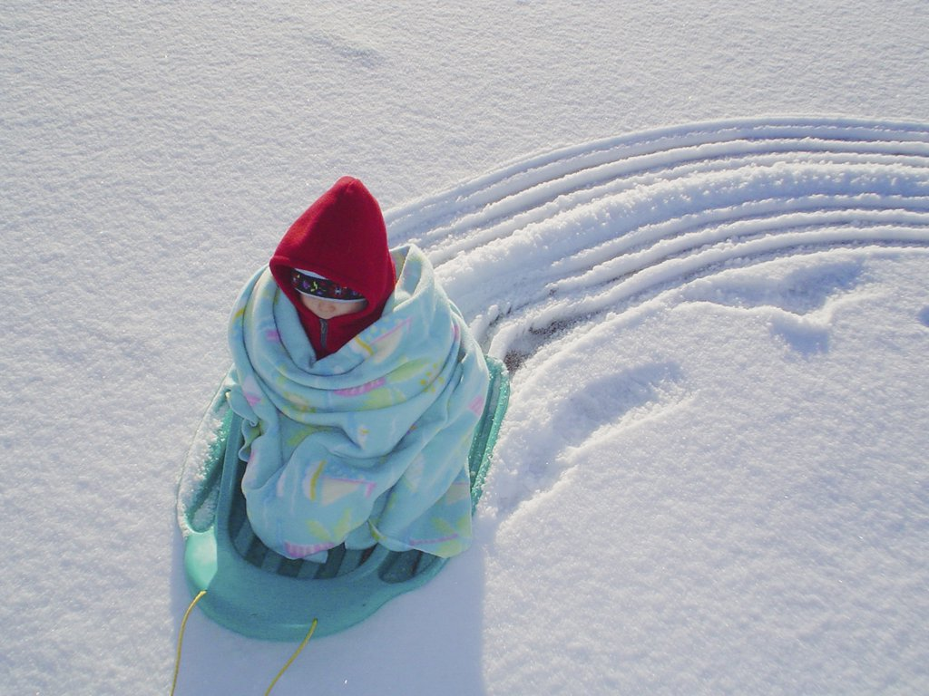 Child Wrapped in a Blanket on a Sled  : Stock Photo