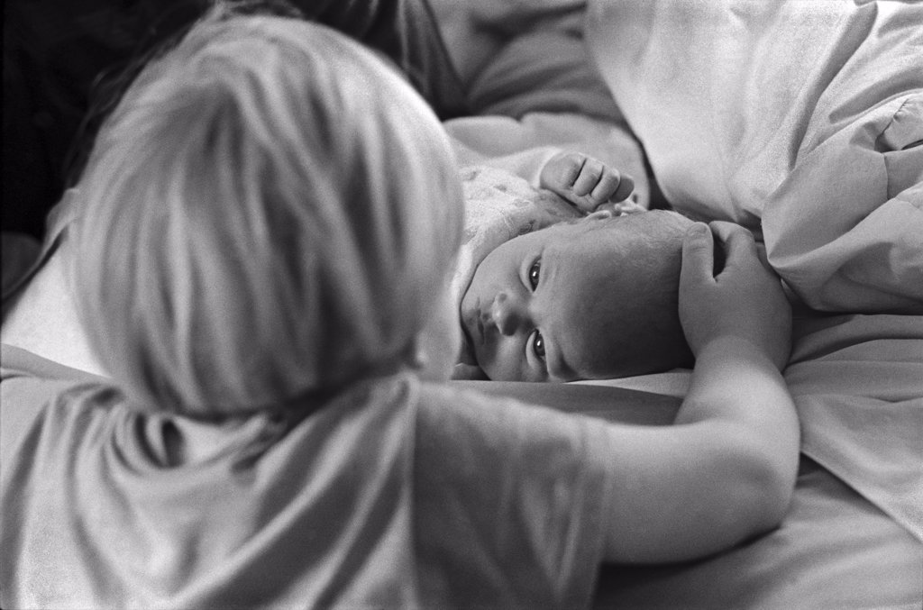 Stock Photo: 1838-13116 Young Boy Looks at Newborn Baby
