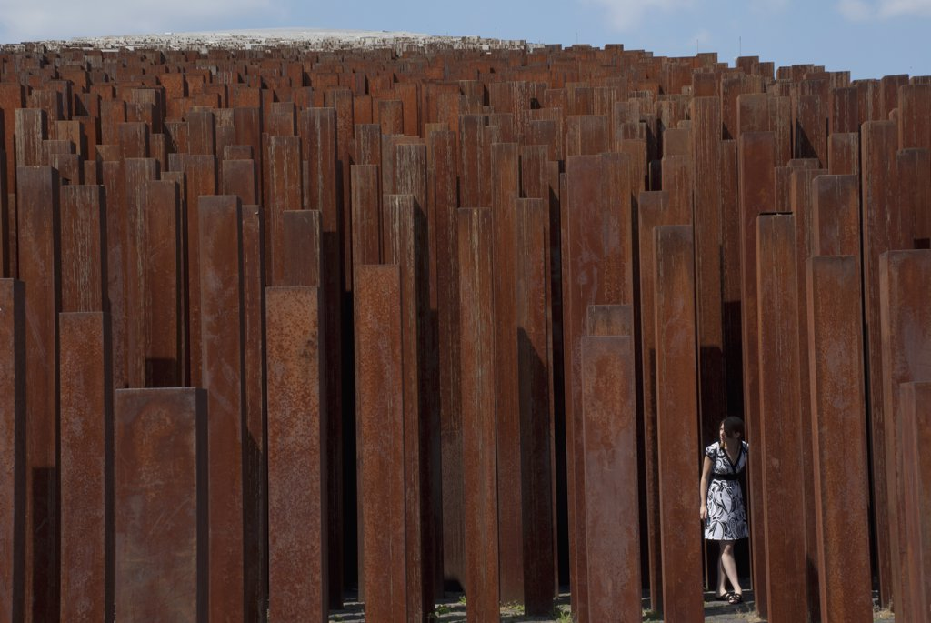 Stock Photo: 1838-13266 Girl Standing Amongst Rusted Iron Pillars