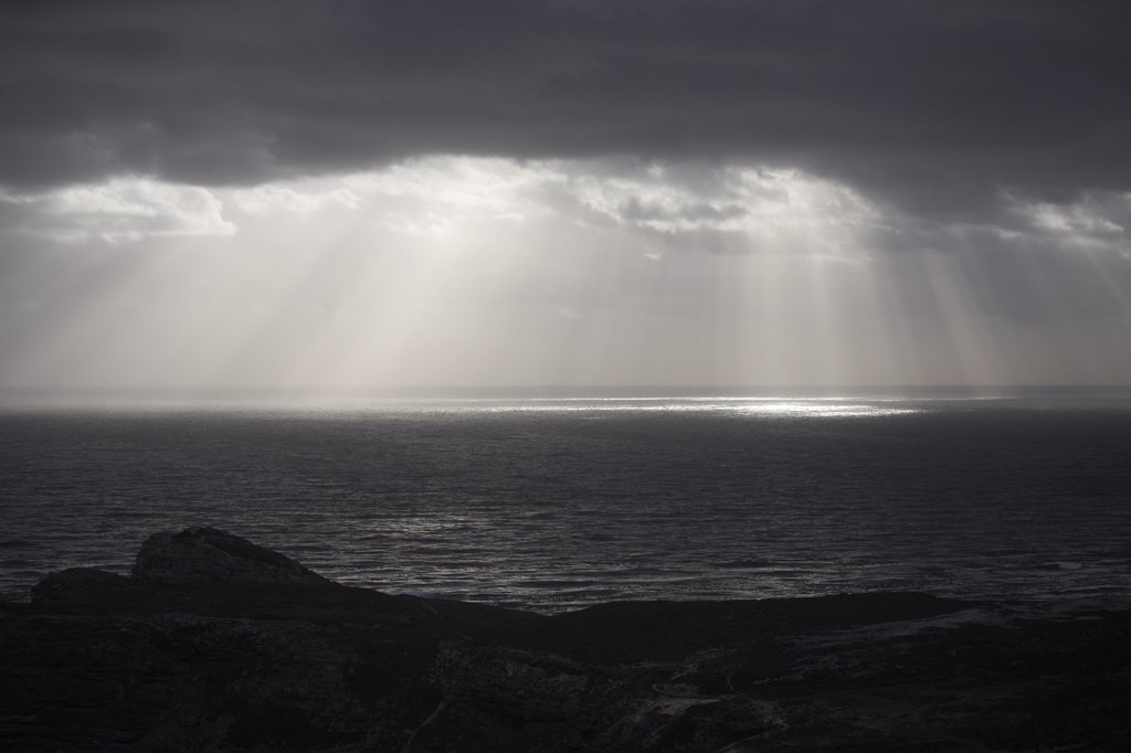 Stock Photo: 1838-13346 Sun Rays Reflected on Ocean Through Gray Clouds