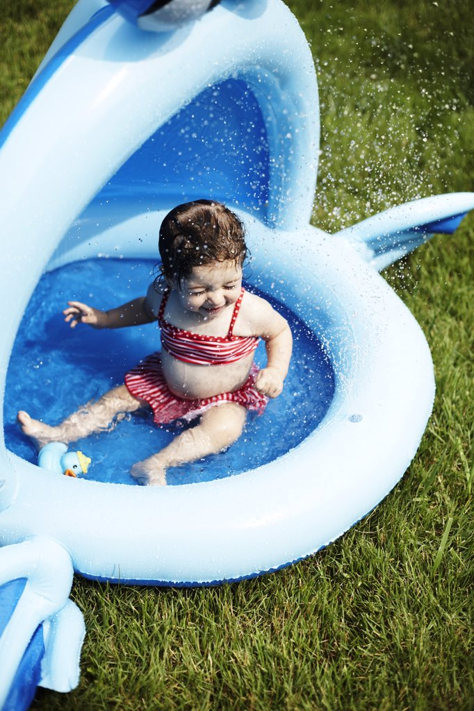 Young Girl in Red Bathing Suit Sitting in Small Pool : Stock Photo
