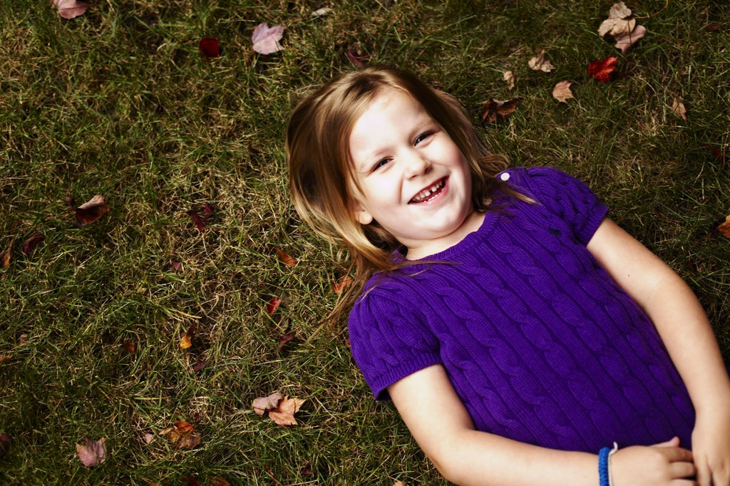 Stock Photo: 1838-13507 Young Smiling Girl Laying on Ground