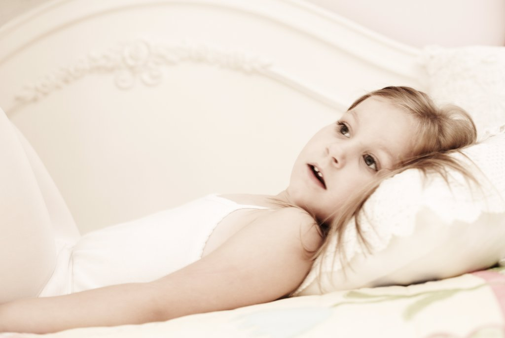 Young Girl Laying on Bed : Stock Photo