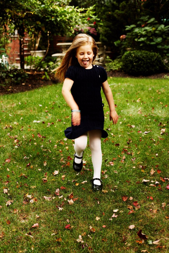 Young Girl in Navy Blue Dress Running in Yard : Stock Photo