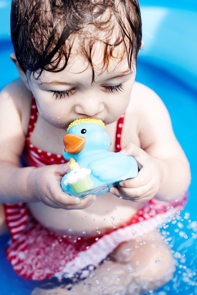 Stock Photo: 1838-13591 Young Girl Sitting in Pool With Rubber Duck