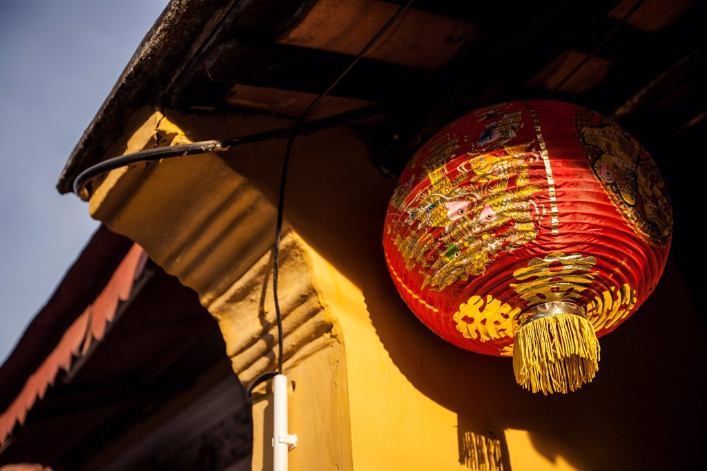 Stock Photo: 1838-13663 Red Paper Lantern Hanging Under Building Eave, Hoi An, Vietnam