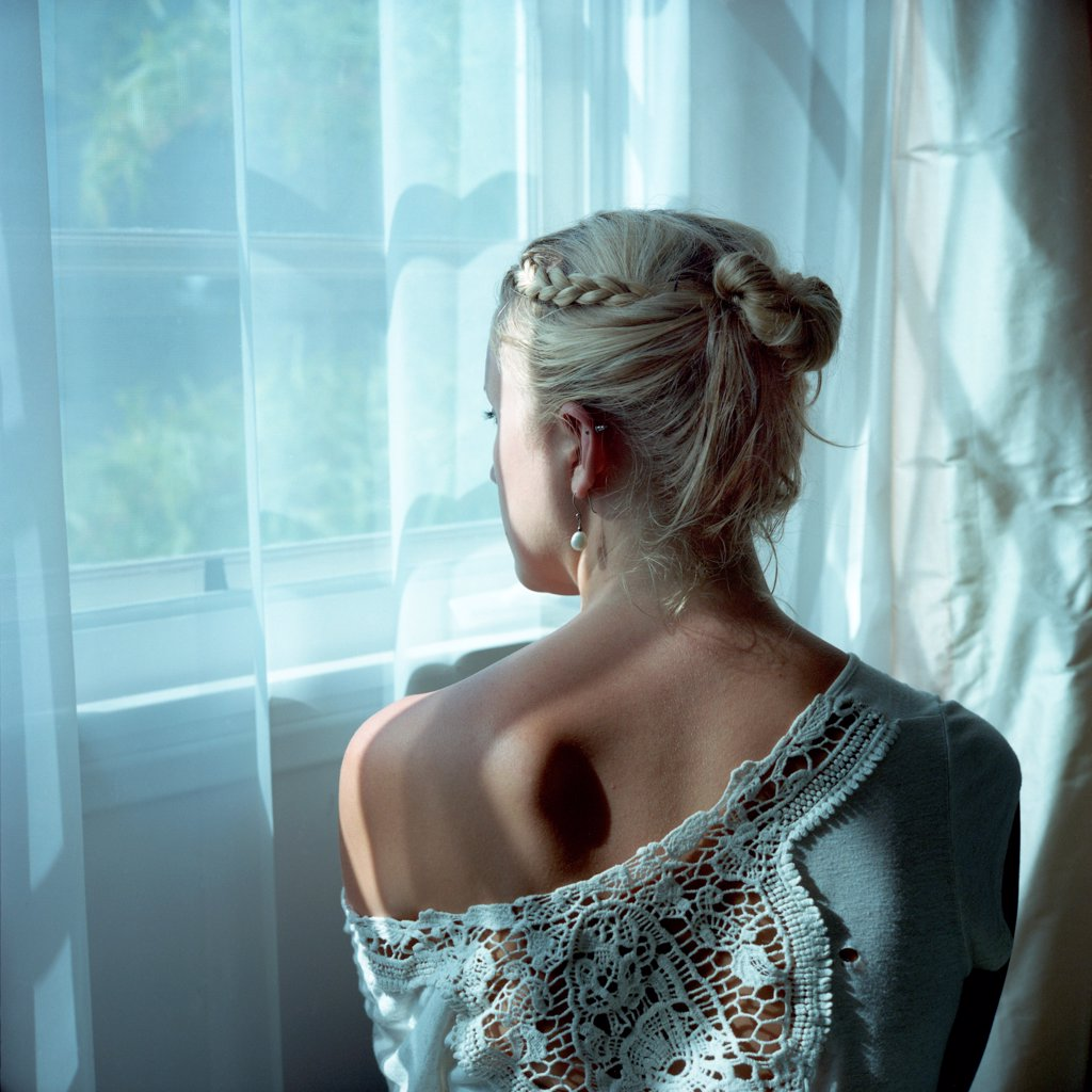 Young Blonde Woman at Window, Rear View : Stock Photo