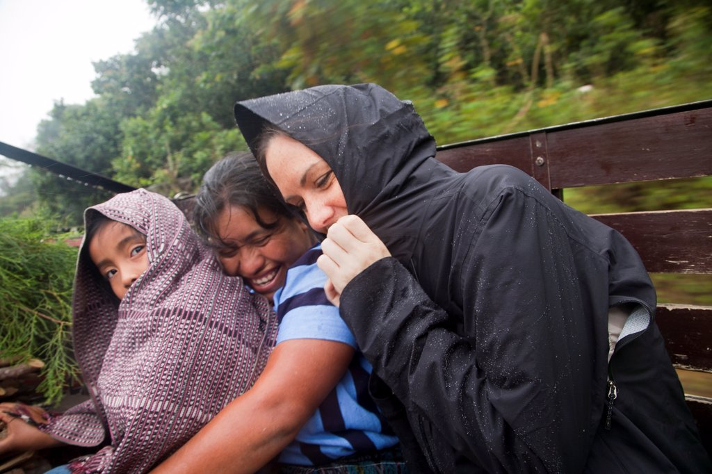 Stock Photo: 1838-13715 Women and Child Riding on Truck in Rain, Guatemala