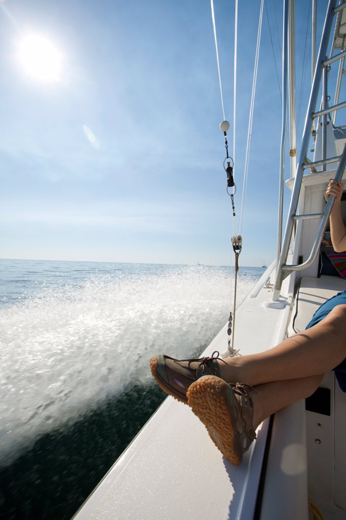 Woman Sitting on Edge of Boat on  Ocean : Stock Photo