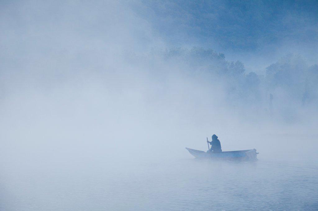 Man Rowing Boat on Misty Lake : Stock Photo