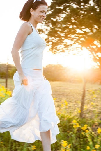 Woman in Long White Skirt Running in Field at Sunset : Stock Photo