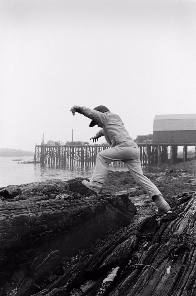Boy Jumping on Rocks Along Shore, Rear View : Stock Photo