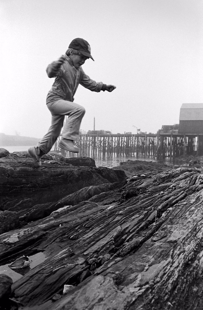 Stock Photo: 1838-13881 Boy Jumping on Rocks Along Shore