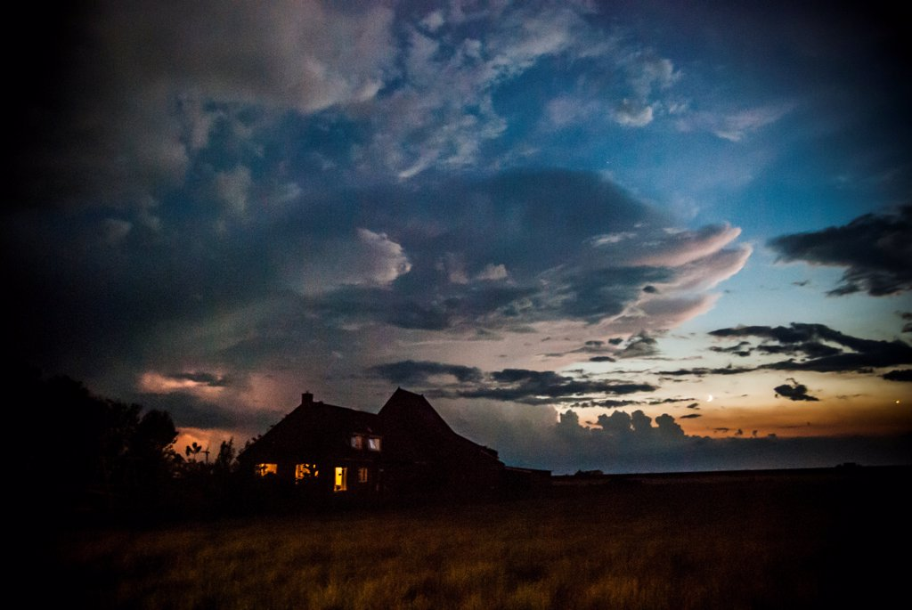 Stock Photo: 1838-13979 Dark Farm House Under Turbulent Sky During Electrical Storm