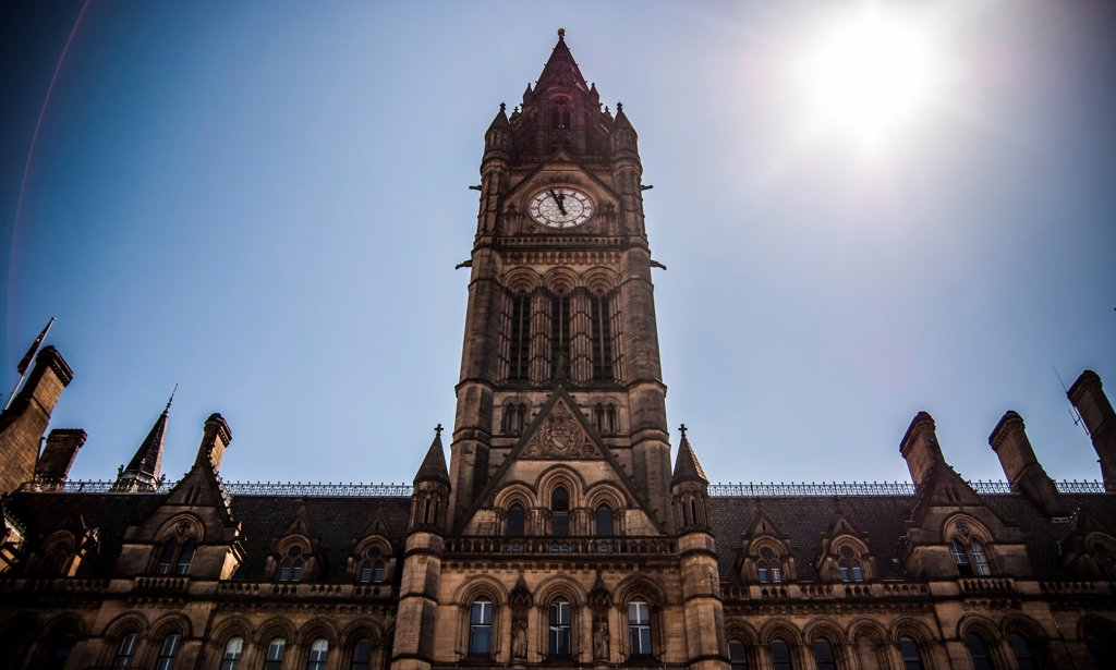 Dramatic Low Angle View of Manchester Town Hall Clock Tower with Sun in Sky, England, UK : Stock Photo