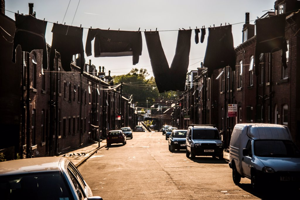 Drying Laundry Hanging from Clothes Line Stretched Across Street, Leeds, England, UK : Stock Photo