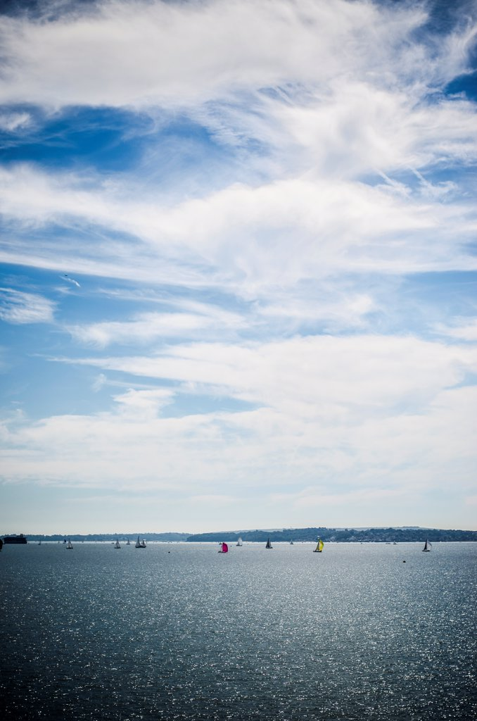 Stock Photo: 1838-14022 Sail Boats in Distant Water Under Blue Sky