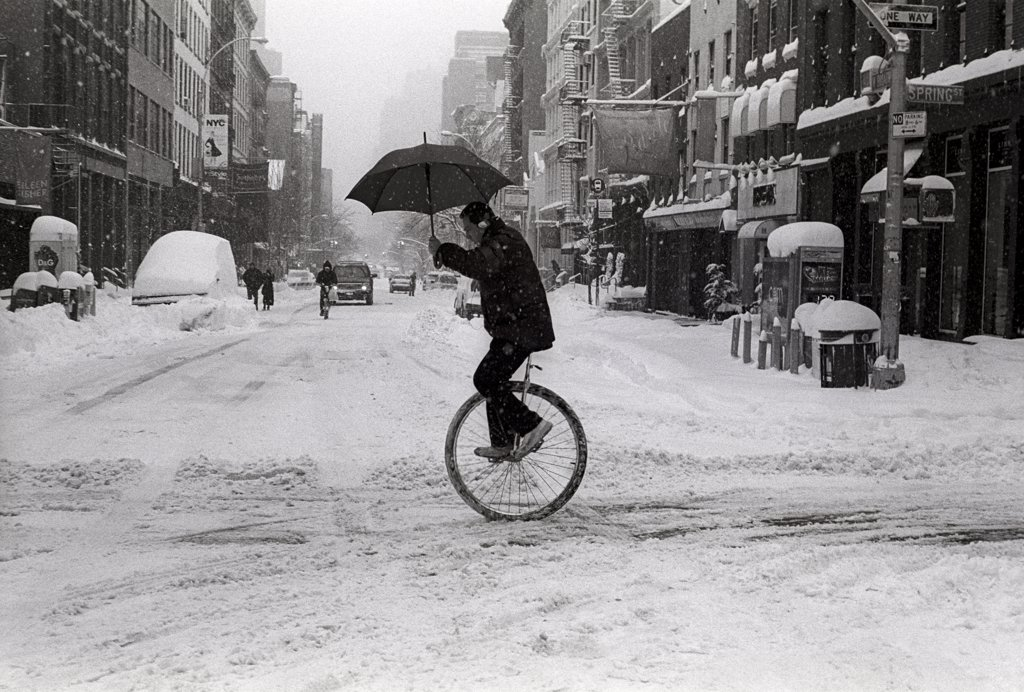 Unicyclist with Umbrella in Winter  : Stock Photo
