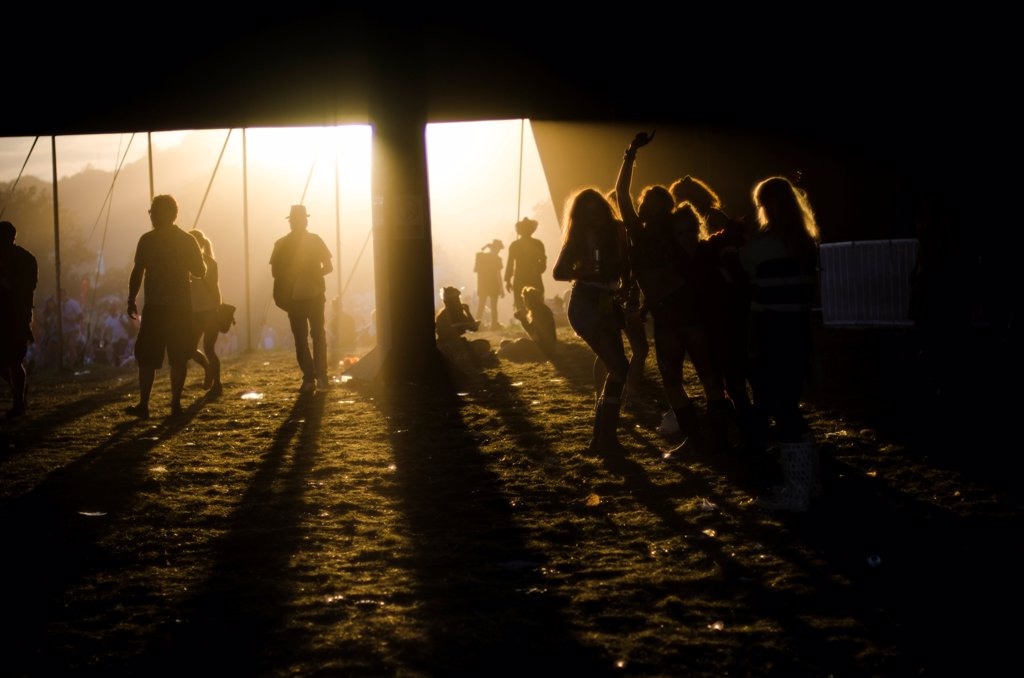 Stock Photo: 1838-14031 Silhouetted Summer Music Festival Goers Under Dark Tent at Sunset, Isle of Wight, UK