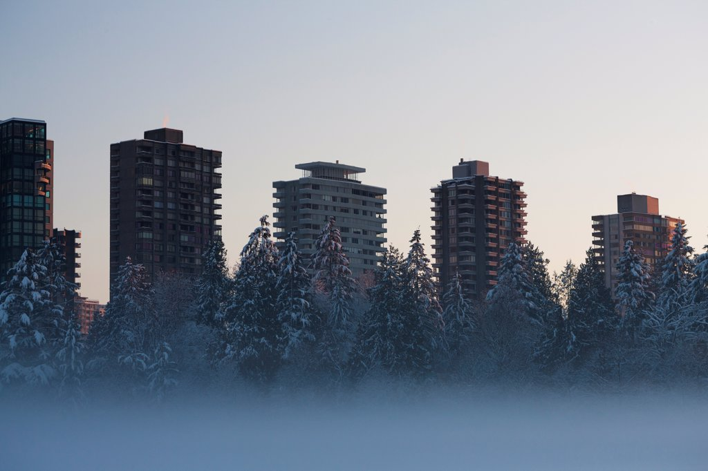 Stock Photo: 1838-14098 Fog on Lake With Snowy Trees and Tall Buildings in Background, Vancouver, Canada