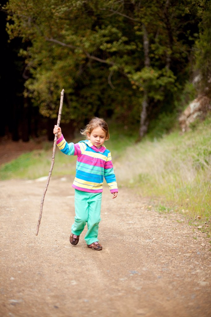 Stock Photo: 1838-14112 Young Girl Walking Along Dirt Road With Walking Stick