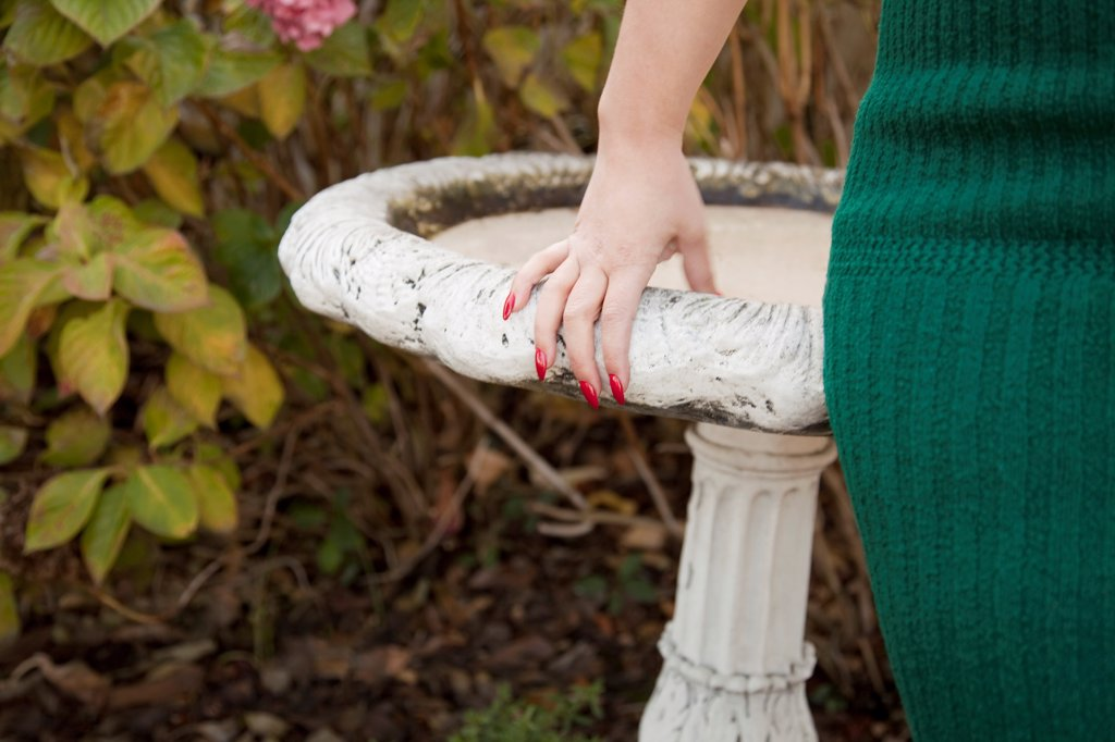 Woman Leaning Against Bird Bath, Close Up : Stock Photo