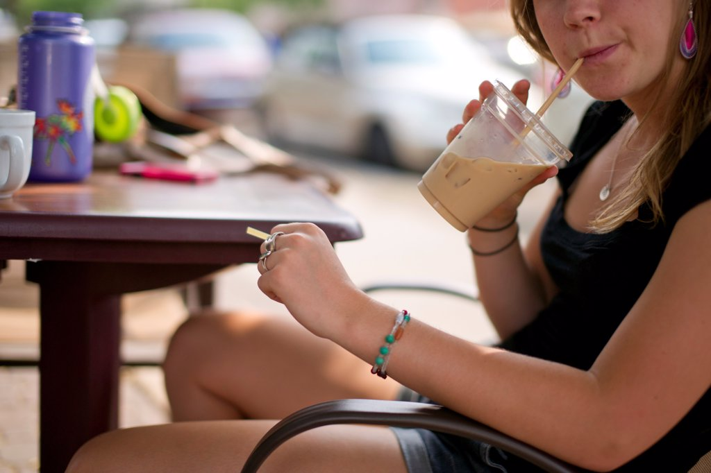 Stock Photo: 1838-14146 Woman Drinking Iced Coffee Drink Through Straw