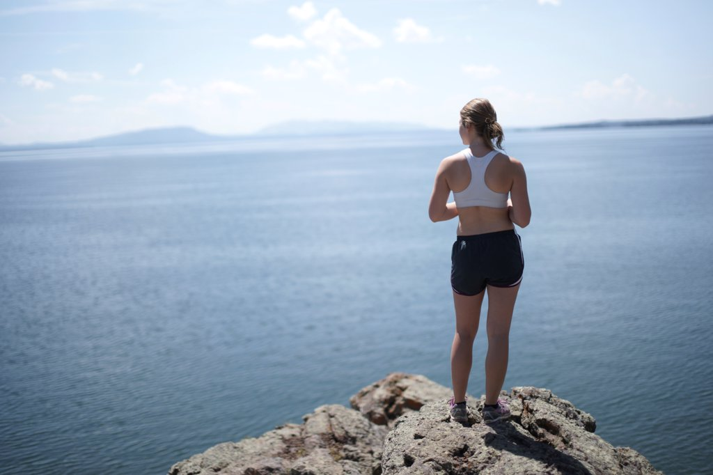Young Female Jogger Staring Out Over Lake : Stock Photo